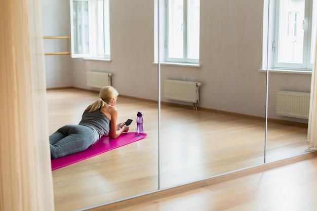 Подходит женщина, проверка ее телефон в тренажерном зале Бесплатные Фотографии