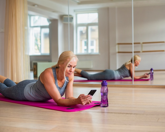 Женщина фитнеса проверяя ее телефон в спортзале Бесплатные Фотографии