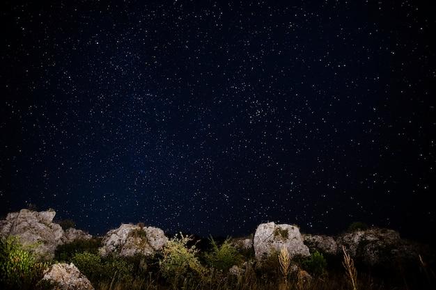 Кристально чистое небо со звездами и камнями на земле Бесплатные Фотографии