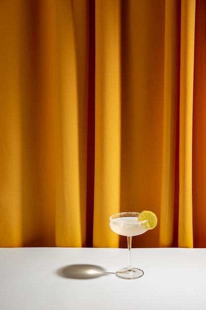 黄色のカーテンに対して白いテーブルに受け皿のグラスでライムカクテル 無料写真