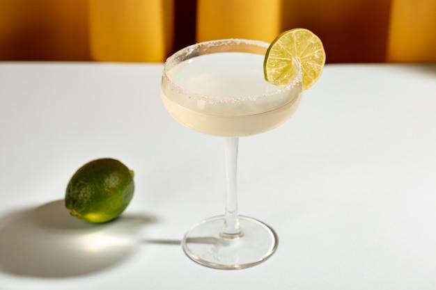 白いテーブルにライムとソーサーグラスでマルガリータカクテル 無料写真