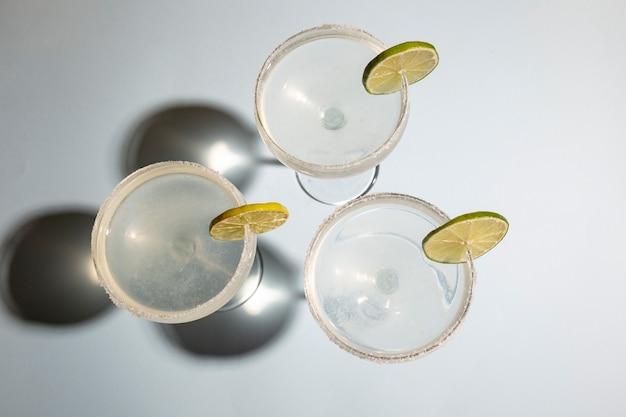 白いテーブルにライムと塩で自家製の古典的なマルガリータ飲み物の高角度のビュー 無料写真