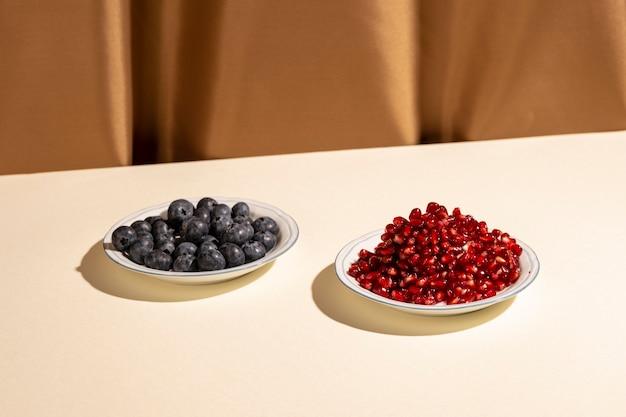 ザクロの種子と茶色のカーテンの近くの白いテーブルの上の皿にブルーベリー 無料写真