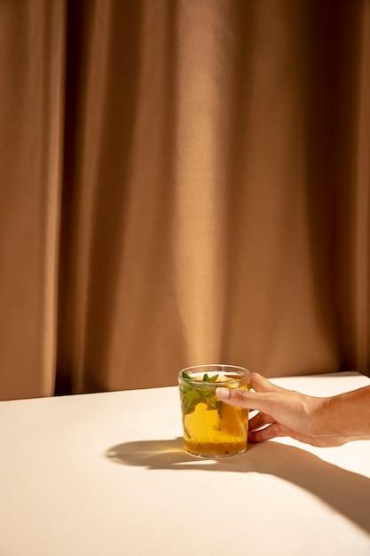 白い机の上のカクテルグラスを取って人の手 無料写真
