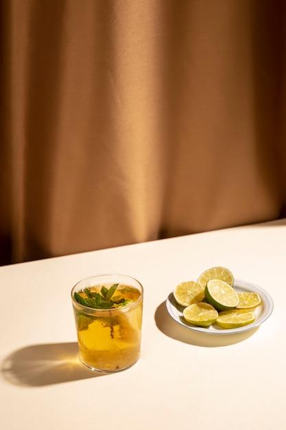 白い机の上のカクテルドリンクとレモンのスライス 無料写真