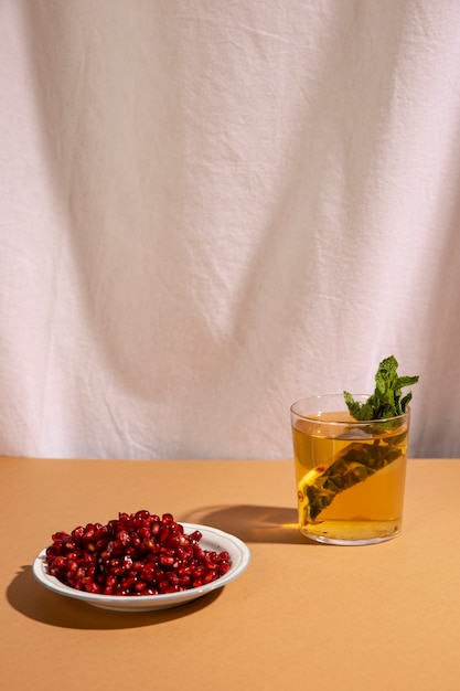 白いカーテンの前にザクロの種子とおいしい飲み物 無料写真