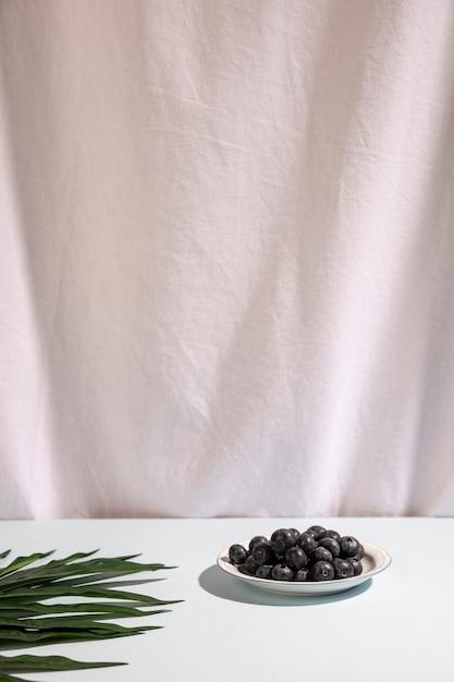 白いカーテンに対してテーブルの上のヤシの葉とプレートの青い果実 無料写真