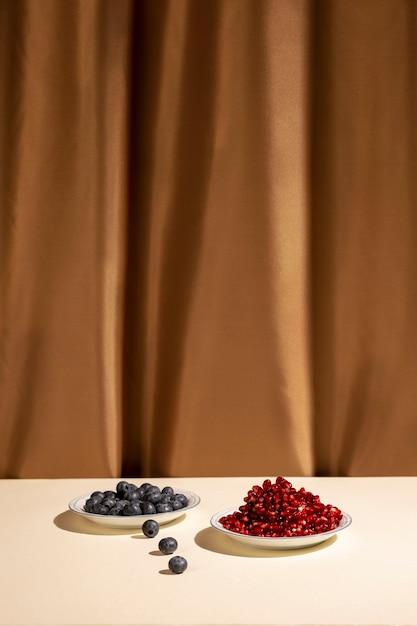 新鮮な青い果実と茶色の背景の前に机の上のジューシーなザクロの種子 無料写真