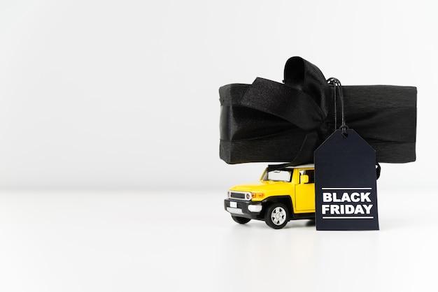 ギフトを運ぶ黒い金曜日のおもちゃの車 無料写真