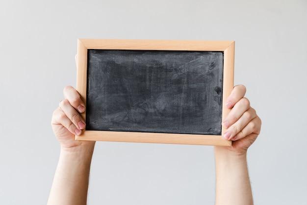 空白の黒板を保持手 無料写真