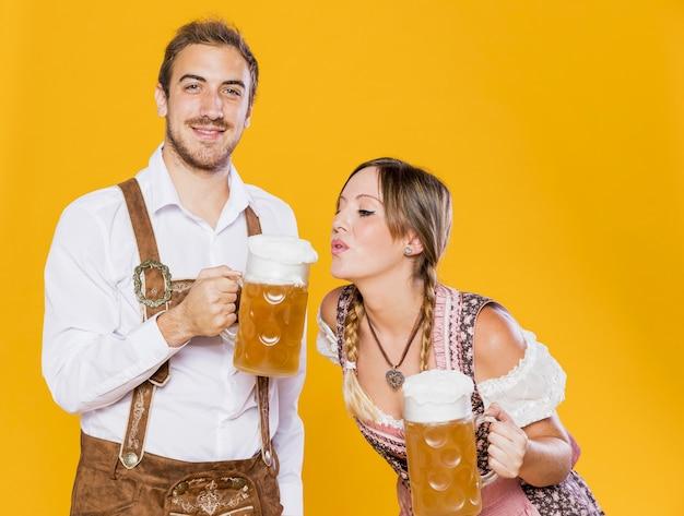 ビールジョッキとバイエルンの若いカップル 無料写真