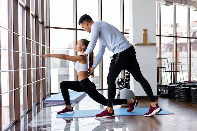 Мужчина помогает женщине с ее тренировкой Бесплатные Фотографии