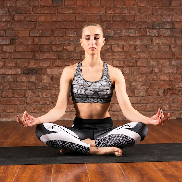 Вид спереди женщина медитирует дома Бесплатные Фотографии