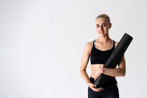 Среднего выстрела женщина с коврик для йоги и копией пространства Бесплатные Фотографии