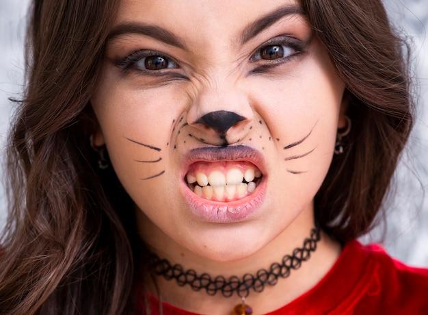 Крупным планом девушка с лицом окрашены на хэллоуин Бесплатные Фотографии