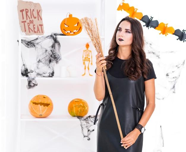 Вид спереди красивая женщина с метлой хэллоуина Бесплатные Фотографии