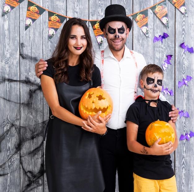 Счастливые родители с сыном позирует на хэллоуин Бесплатные Фотографии