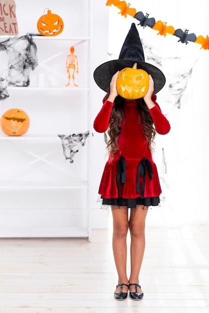 ハロウィーンのカボチャを保持しているフルショット若い女の子 無料写真