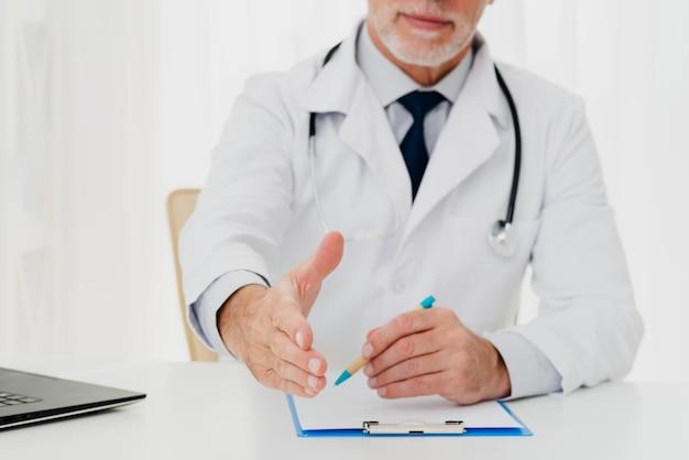座っている間彼の手を保持している医者 無料写真