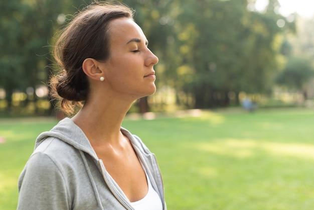 Вид сбоку женщина с закрытыми глазами на открытом воздухе Бесплатные Фотографии