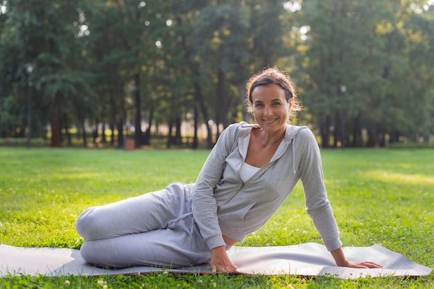 Полная съемка счастливая женщина сидя на циновке йоги Бесплатные Фотографии
