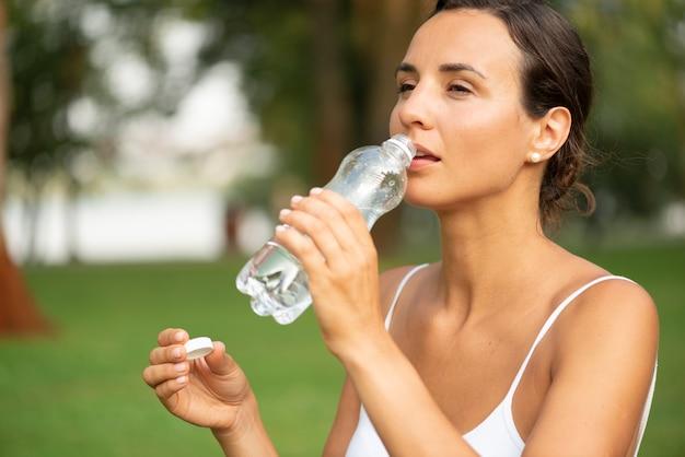 水を飲む女性のミディアムショット 無料写真