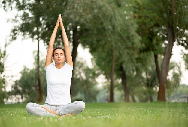座っていると瞑想のフルショット女性 無料写真