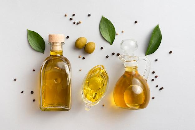 Оливковое масло на столах с листьями и оливками Бесплатные Фотографии
