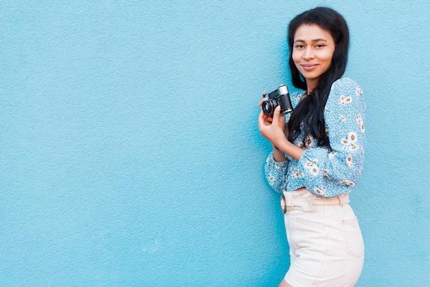 カメラを保持している花のブラウスを持つ女性 無料写真
