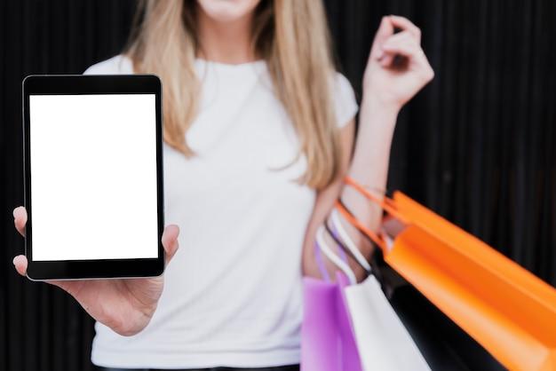 タブレットのモックアップを保持している買い物袋を持つ少女 無料写真