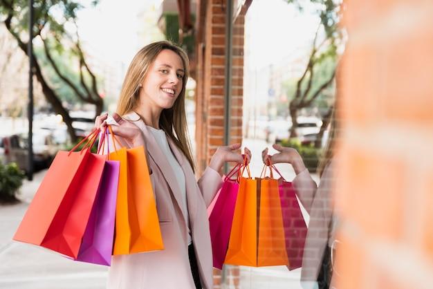 ウィンドウの前に立っている買い物袋を持つ少女 無料写真