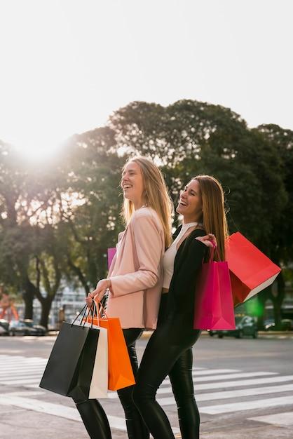 路上で買い物袋を持つ少女の笑顔 無料写真
