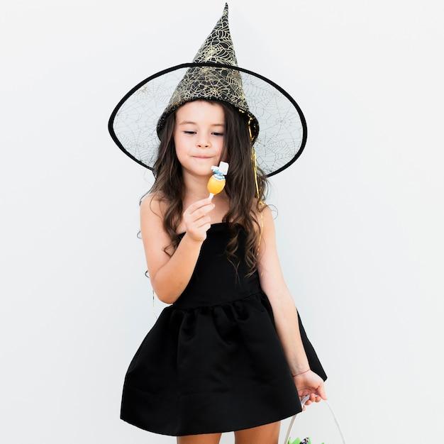 ハロウィーンの魔女の衣装の少女を正面します。 無料写真