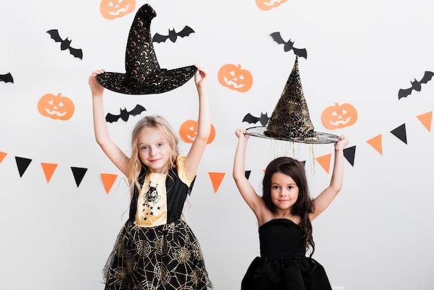 Вид спереди маленьких девочек в костюме ведьмы на хэллоуин Бесплатные Фотографии
