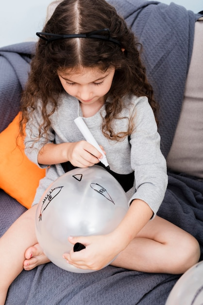 Маленькая девочка, рисование на воздушном шаре на хэллоуин Бесплатные Фотографии