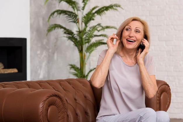 電話で話しているスマイリー女性 無料写真