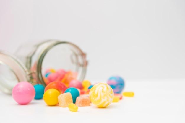テーブルの上においしいお菓子とひっくり返った瓶 無料写真
