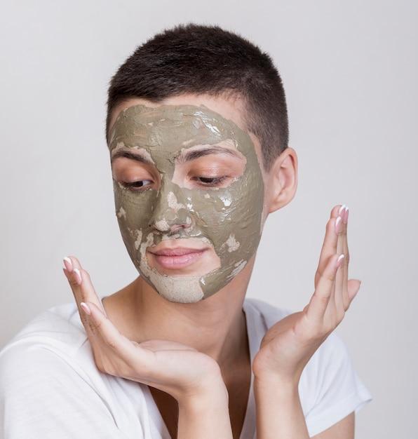 下へ見ている顔のマスクを持つ女性 無料写真