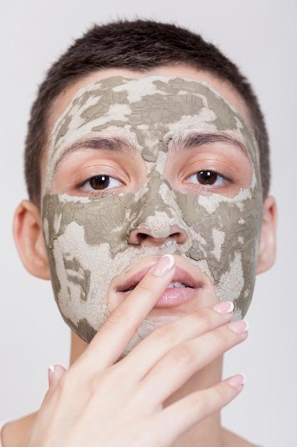 カメラのクローズアップを見て顔のマスクを持つフロントビュー女性 無料写真