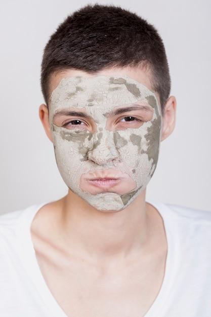 カメラを見て顔のマスクを持つモデル 無料写真