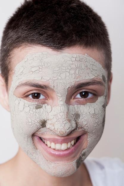 カメラのクローズアップを見てフェイスマスクを持つ若い女性 無料写真