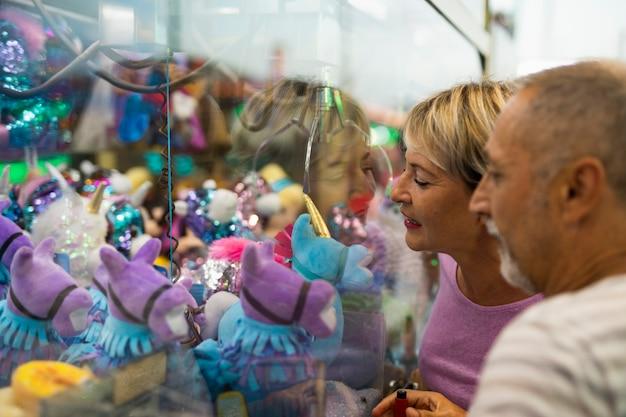 おもちゃを見てサイドビューの人々 無料写真