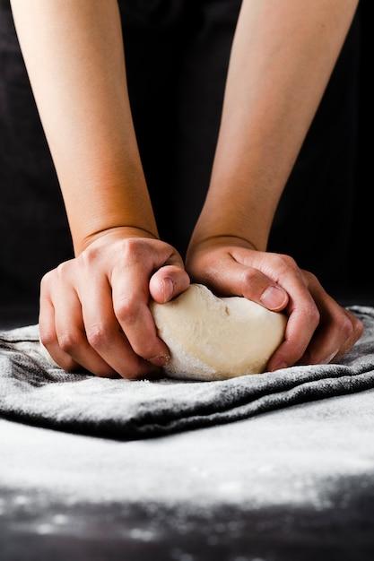 手と黒い背景と生地の正面図 無料写真