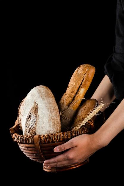 パンのバスケットを保持している手の正面図 無料写真