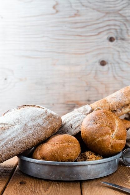 木製のテーブルのトレイ上のパンの正面図 無料写真