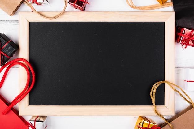 Пустая доска в окружении подарочных пакетов Бесплатные Фотографии