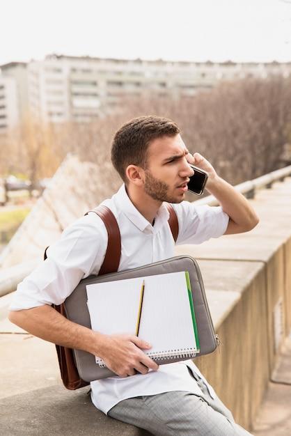 電話で話していると離れている白いシャツの男 無料写真
