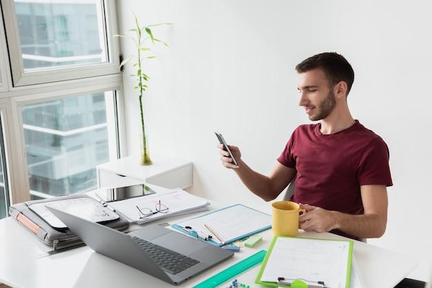 オフィスの机に座っている男の長い眺め 無料写真
