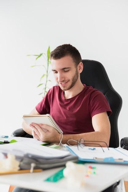 彼のノートを見てゲームの椅子に座っている男 無料写真
