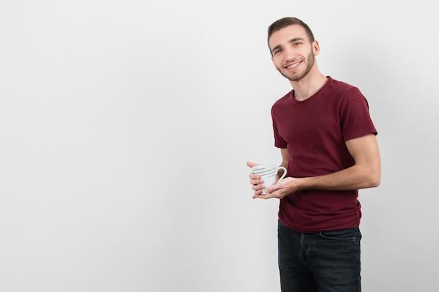 一杯のコーヒーと笑顔を保持している男 無料写真
